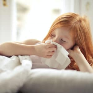 child blowing nose